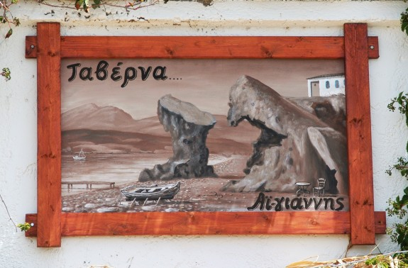 This painting hangs above the Agios Yiannis Taverna. The Church of the Theotokos is painted in the top right corner of the painting. The Church is located up a steep walk approximately 100 yards away, on a cliff, looking over the sea and the Taverna below.